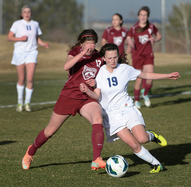 . ARVADA, CO - MARCH 19: Chatfield midfielder Carly George (12) vied for the ball with Ralston Valley midfielder Lindsay Guerrero (19) in the first half.  The Ralston Valley High School girl\'s soccer team defeated Chatfield 3-2 with an overtime goal by sophomore forward Emma Musson Wednesday evening, March 19, 2014. (Photo by Karl Gehring/The Denver Post)