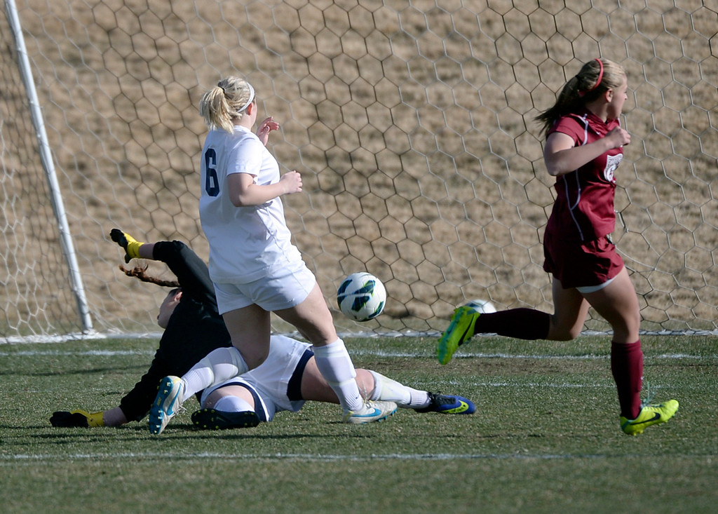 . ARVADA, CO - MARCH 19: Chatfield freshman Bree Bezdek (14) beat Ralston Valley goalie Renee Roemer for a goal in the second half. The Ralston Valley High School girl\'s soccer team defeated Chatfield 3-2 with an overtime goal by sophomore forward Emma Musson Wednesday evening, March 19, 2014. (Photo by Karl Gehring/The Denver Post)