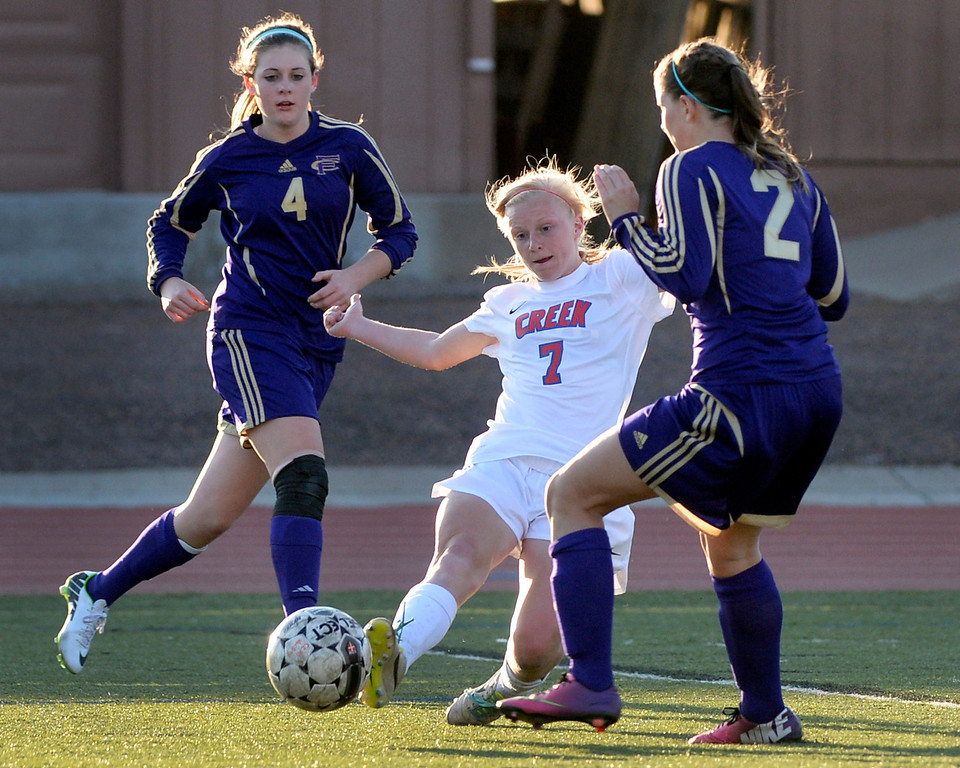 . GREENWOOD VILLAGE, CO - MARCH 25: Creek freshman midfielder Meg Halvorson (7) tried to sneak a pass between Fort Collins defenders Shannon Duff (4) and Nicole Dietrich (2) in the first half. The Cherry Creek High School girl\'s soccer team defeated Fort Collins 3-2 at the Stutler Bowl Tuesday night, March 25, 2014. (Photo by Karl Gehring/The Denver Post)