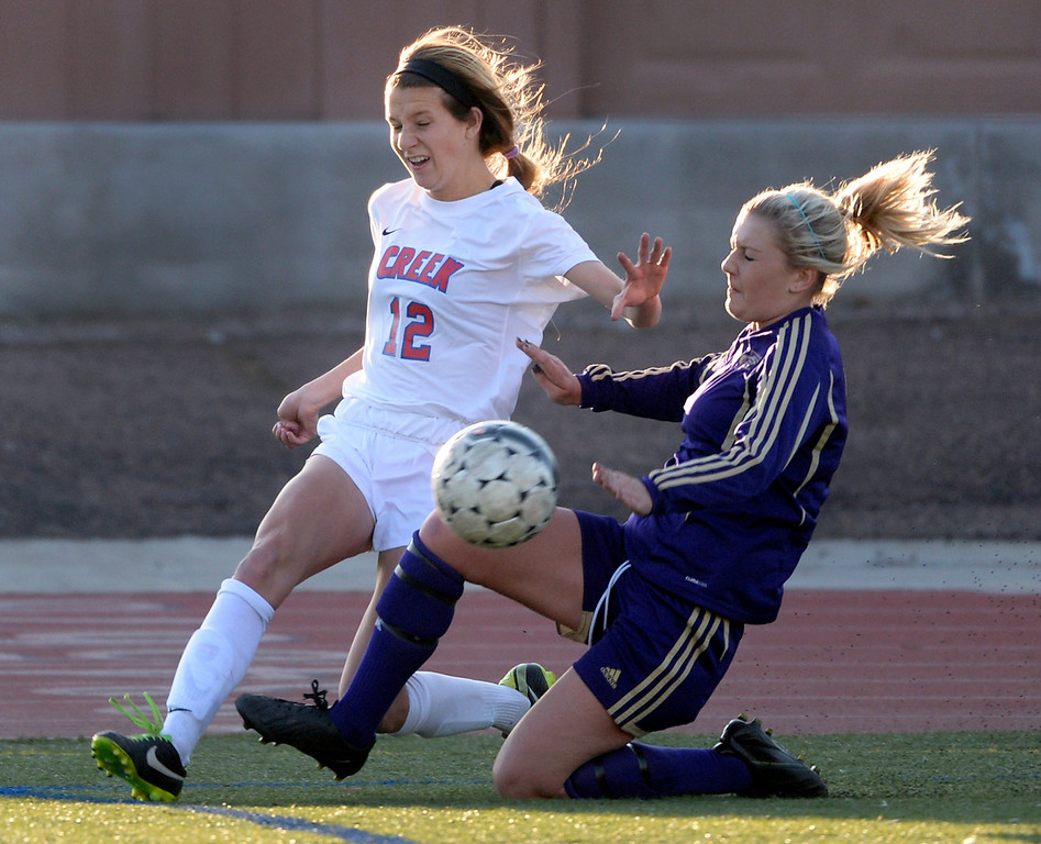 . GREENWOOD VILLAGE, CO - MARCH 25: Creek junior midfielder Ryan Williams (12) tried to get a centering pass past Fort Collins defender Aubrey Weapppa (7) in the first half.  The Cherry Creek High School girl\'s soccer team defeated Fort Collins 3-2 at the Stutler Bowl Tuesday night, March 25, 2014. (Photo by Karl Gehring/The Denver Post)