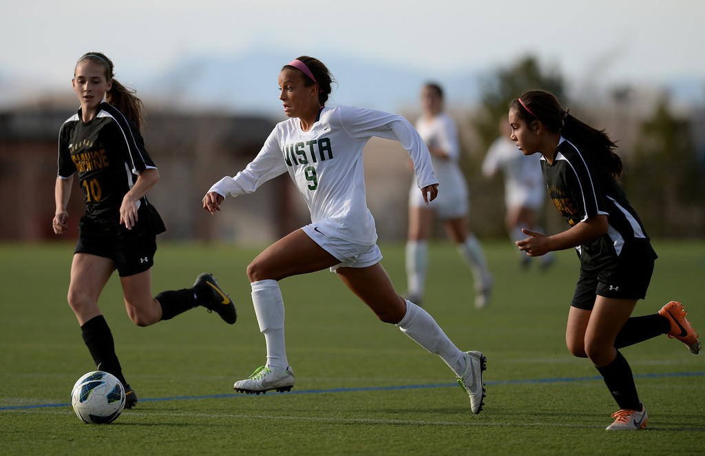 . Mallory Pugh of Mountain Vista High School (9), center, controls the ball between Jacqueline Pepper (10) and Elena Jauregui (2) of Arapahoe High School in the second half of the game at Shea Stadium in Highlands Ranch, Colorado on March 29, 2014. Mountain Vista won, 5-4. (Photo by Hyoung Chang/The Denver Post)