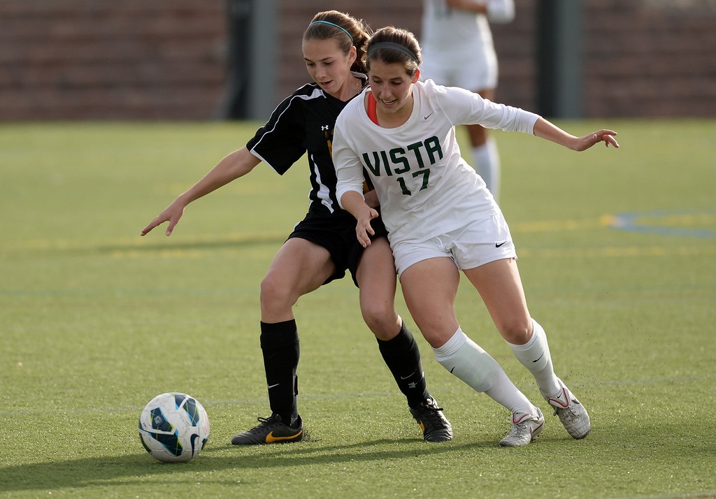 . Morgan McDougal of Mountain Vista High School (17) challenges Jacqueline Pepper (10)  of Arapahoe High School during the game at Shea Stadium in Highlands Ranch, Colorado on March 29, 2014. Mountain Vista won, 5-4. (Photo by Hyoung Chang/The Denver Post)