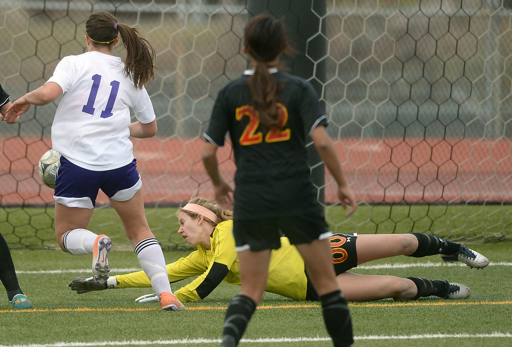 . Castle View goalkeeper Danielle Williams (00) deflected a shot away from Littleton midfielder Laura Puchino (11) in the first half. The Littleton High School girl\'s soccer team played Castle View to a scoreless tie Tuesday afternoon, April 1 in Littleton.  (Photo by Karl Gehring/The Denver Post)