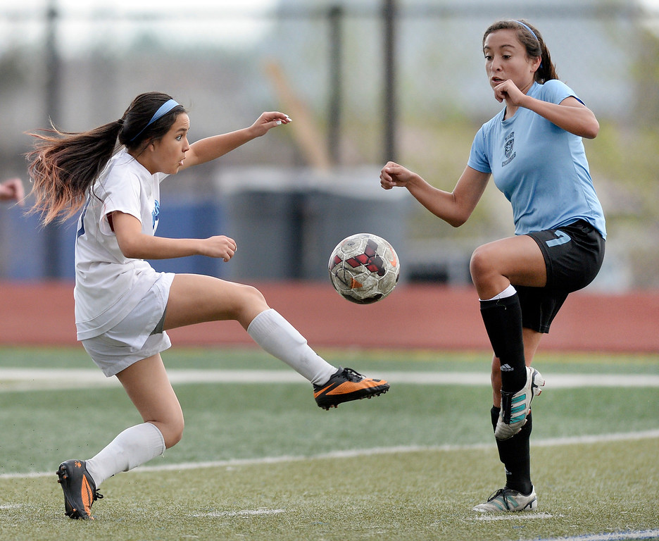 . Valor sophomore midfielder Amanda Lopez, left, competed for the ball with Pueblo West midfielder Deanna Rangel, right, in the first half. The Valor Christian High School girl\'s soccer team defeated Pueblo West 4-1 Wednesday night, May 7, 2014 in the first round of the playoffs. (Photo by Karl Gehring/The Denver Post)