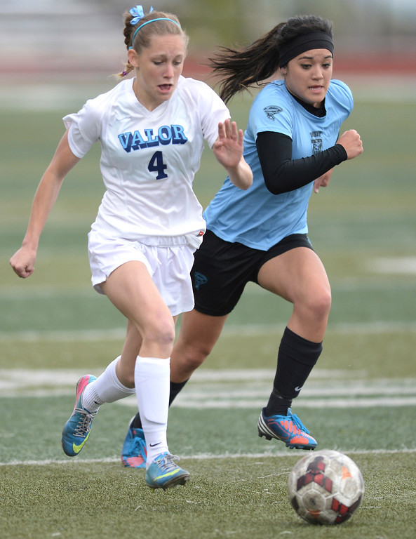 . Valor junior midfielder Maddison Thompson, left, and Pueblo West midfielder Mikaela Oles, right, chased after the ball in the first half. The Valor Christian High School girl\'s soccer team defeated Pueblo West 4-1Wednesday night, May 7, 2014 in the first round of the playoffs. (Photo by Karl Gehring/The Denver Post)