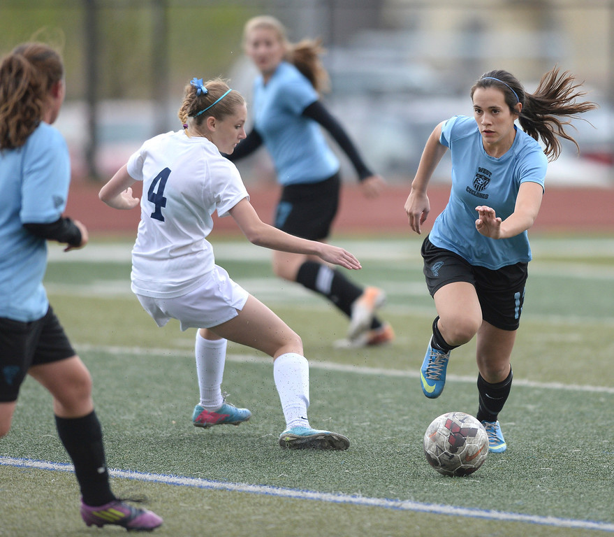 . HIGHLANDS RANCH, CO - MAY 7: Pueblo West senior defender Fabiana Molina (13) cleared the ball away from Valor junior midfielder Maddison Thompson (4) in the first half. The Valor Christian High School girl\'s soccer team defeated Pueblo West 4-1 Wednesday night, May 7, 2014 in the first round of the playoffs. (Photo by Karl Gehring/The Denver Post)