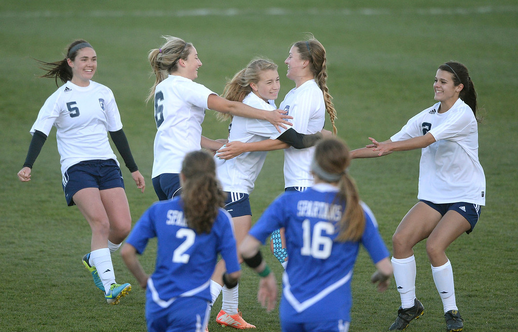 . The Rebels celebrated with midfielder Kelcey Cavarra (4) after she put in the game winning goal late in the second half.  (Photo by Karl Gehring/The Denver Post)