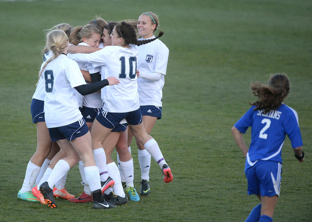 . The Rebels surrounded Kelcey Cavarra after she put in the game winning goal late in the second half.  (Photo by Karl Gehring/The Denver Post)