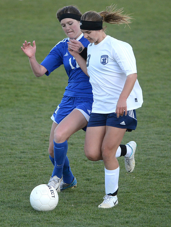 . Doherty defender Madison Furbush (17) tried to slow down Columbine forward Amanda Porter (13) in the second half. The Columbine High School girl\'s soccer team defeated Doherty 3-1 in a 5A quarterfinal game Tuesday night, May 13, 2014. (Photo by Karl Gehring/The Denver Post)