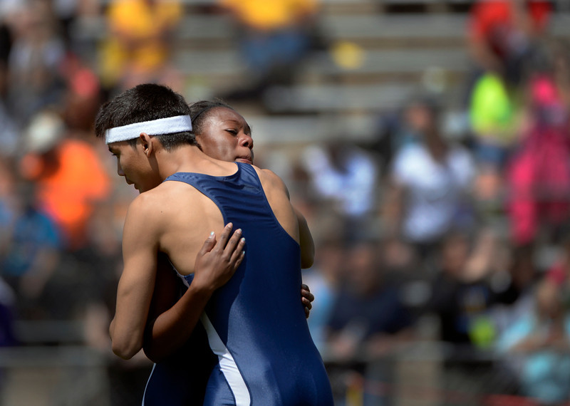 . Teammates Alicia Lawrence and Miguel Molas greet each other with a hug after competing in the Boys/Girls 3A 100 Meter Dash event. The Colorado State High School Track and Field meet takes place at Jeffco Stadium in Lakewood on Saturday, May 17, 2014. (Kathryn Scott Osler, The Denver Post)