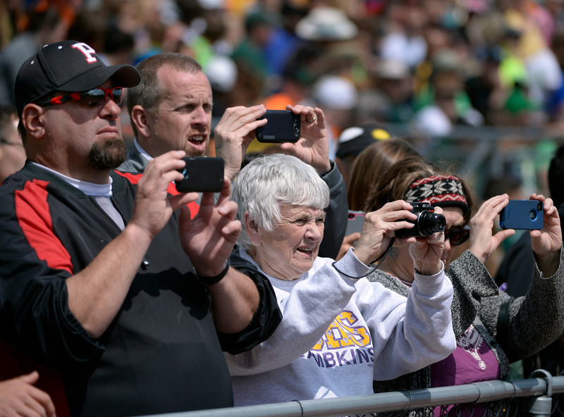 . Spectators gather at the edge of the fence in hopes of getting a photo of the winner getting their medals on the podium. The Colorado State High School Track and Field meet takes place at Jeffco Stadium in Lakewood on Saturday, May 17, 2014. (Kathryn Scott Osler, The Denver Post)