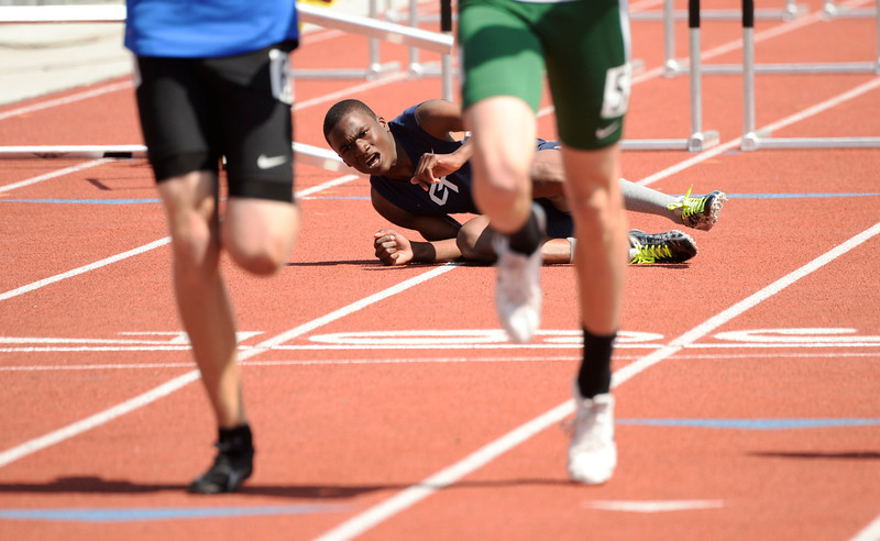 . Jordan Wright, of Cherokee Trail High School, watches other runners cross the finish after falling in 5A qualifying 110m hurdles at the Colorado High School State Track and Field Championships, May 15, 2014. Action will continue through Saturday at Jeffco Stadium in Lakewood. (Photo by RJ Sangosti/The Denver Post)