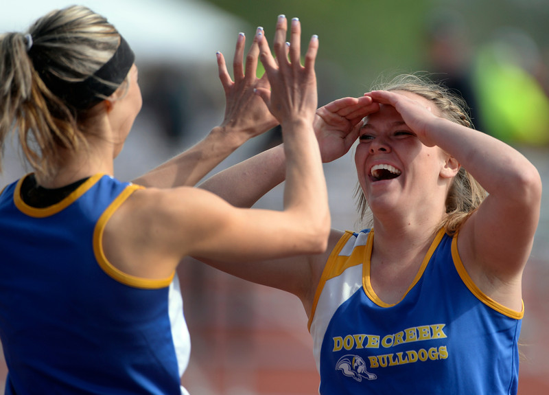 . Corissa Guynes, right,  from Dove Creek is congratulated by teammate Shelbie Knuckles after Guynes won the 1A Girls 100 Meter Hurdles event. The Colorado State High School Track and Field meet takes place at Jeffco Stadium in Lakewood on Saturday, May 17, 2014. (Kathryn Scott Osler, The Denver Post)