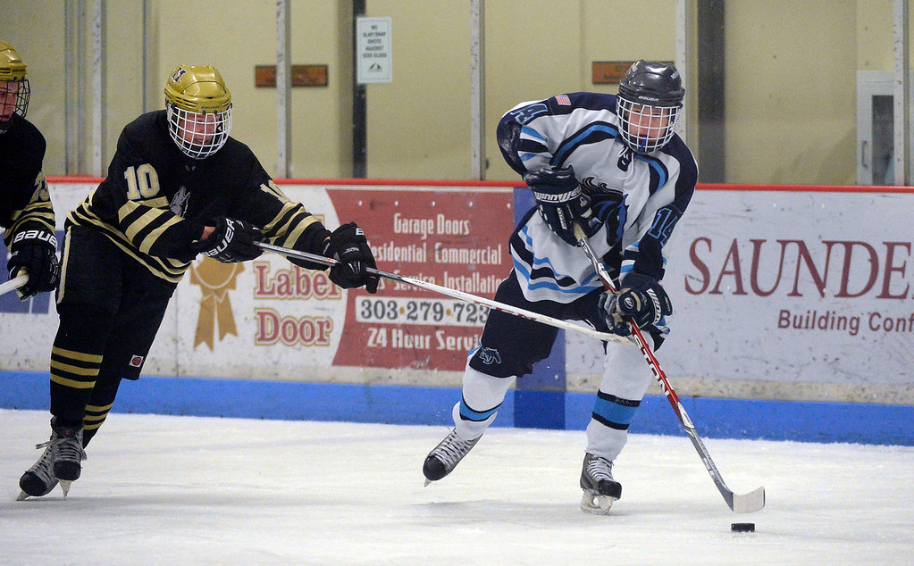 . Ralston Valley Ian Oughton (14) skates the puck down ice as he gets chased by Monarch Kevin Palm (10) during the second period January 14, 2014 at Apex Ice Arena. (Photo by John Leyba/The Denver Post)