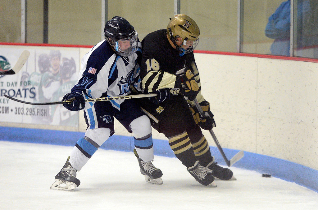 . Ralston Vally Austin Resseguie (11) chases the puck with Monarch David Neithenbach (18) during the first period January 14, 2014 at Apex Ice Arena. (Photo by John Leyba/The Denver Post)