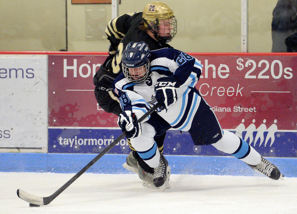 . Monarch Cameron Gardner (23) knocks down Ralston Valley Hunter Schoepflin (28) as he tries to control the puck during the first period January 14, 2014 at Apex Ice Arena. (Photo by John Leyba/The Denver Post)