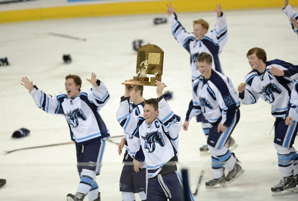 . Victor Lombardi of Ralston Valley High School (12), holds up the trophy, and teammates celebrate winning of Colorado High School State Championship Hockey game against Monarch High School at the Denver Coliseum. Denver, Colorado. March 1, 2014. Ralston Valley won 4-1. (Photo by Hyoung Chang/The Denver Post)
