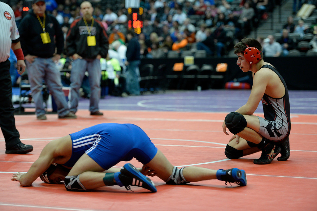 . Sergio Chavez of Hinkley (L) grimaces as he grabs his right knee during his match with Jason Romero of Pomona in class 5A 132 pound match on the first day of Colorado High School State Wrestling February 20, 2014 Pepsi Center. The match was stopped as Chavez couldn\'t continue with his knee injury. (Photo by John Leyba/The Denver Post)