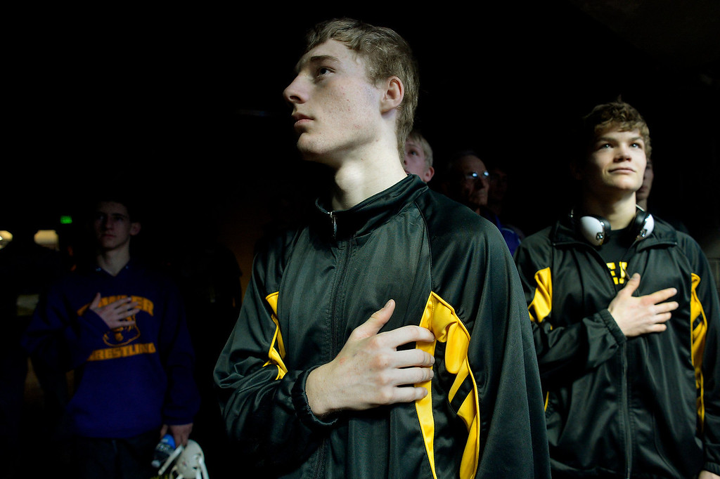 . DENVER, CO. - FEBRUARY 22: Seniors Aaron Cochran, left, and J.C. Henderson of Meeker High School listen to the National Anthem before the consolation rounds of the Colorado State Wrestling Championship at the Pepsi Center in Denver, CO February 22, 2014. (Photo By Craig F. Walker / The Denver Post)