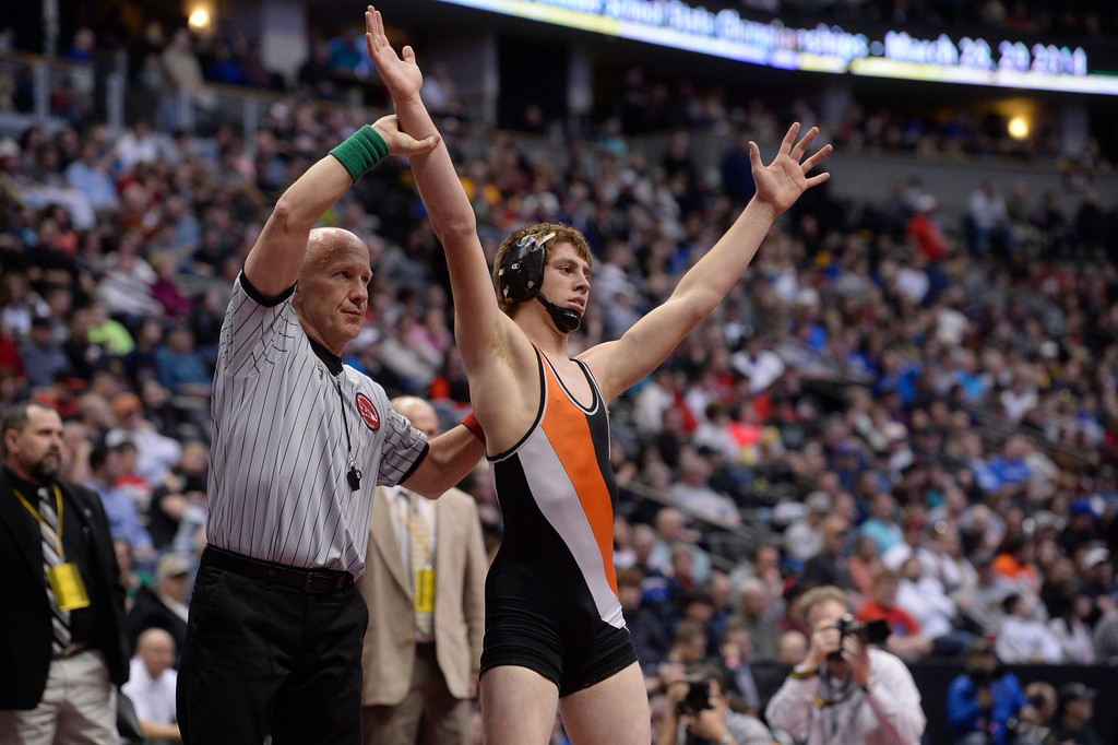 . DENVER, CO - FEBRUARY 22: Joel Contreras of Sterling (in black and orange) celebrates after winning the 3A 145lb. championship match. The Colorado Wrestling Tournament was held at the Pepsi Center in Denver, Colo. on February 22, 2014. (Photo by Andy Cross/The Denver Post)