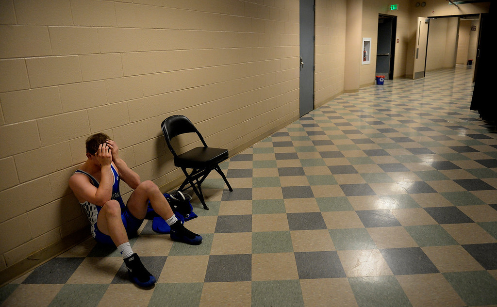 ". DENVER, CO. - FEBRUARY 22: Senior Drake Greeott of Longmont High School sits in the hallway after his loss in the Colorado State Wrestling Championship at the Pepsi Center in Denver, CO February 22, 2014. Greeott said he started strong in the 4A 160-pound consolation match, ""then he got a couple of back points and I got a couple of stalling calls... it\'s hard.\"" (Photo By Craig F. Walker / The Denver Post)"