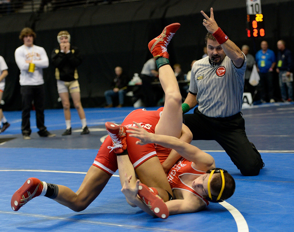 . DENVER, CO - FEBRUARY 20: Maya Nelson of Denver East earns two points against Carl Camposanto of Regis during their 5A 106 pound match on the first day of Colorado High School State Wrestling February 20, 2014 Pepsi Center. Maya defeated Camposanto 13-9.  (Photo by John Leyba/The Denver Post)