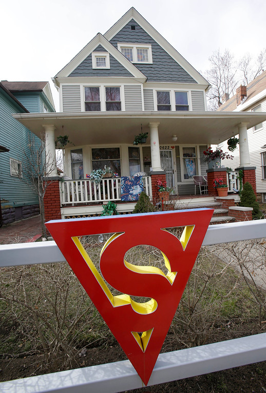 ". In this Tuesday, April 2, 2013 photo shows the red ""S\"" on a fence outside the home of Jerry Siegel in Cleveland. Superman collaborators Siegel and Joe Shuster lived several blocks apart in the Glenville neighborhood which shaped their lives, dreams for the future and their imagery of the Man of Steel. (AP Photo/Tony Dejak)"