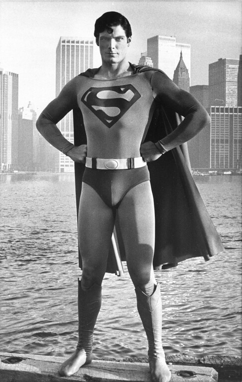 ". Actor Christopher Reeve poses as Superman at the Brooklyn waterfront with a view of lower Manhattan behind him during filming for the movie ""Superman\"" in 1977.  (AP Photo)"