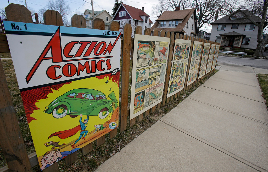 . In this Tuesday, April 2, 2013 photo shows oversized Superman comic book pages displayed on a fence outside of what was once Joe Shuster\'s boyhood home in Cleveland. Superman collaborators Jerry Siegel and Shuster lived several blocks apart in the Glenville neighborhood which shaped their lives, dreams for the future and their imagery of the Man of Steel. (AP Photo/Tony Dejak)