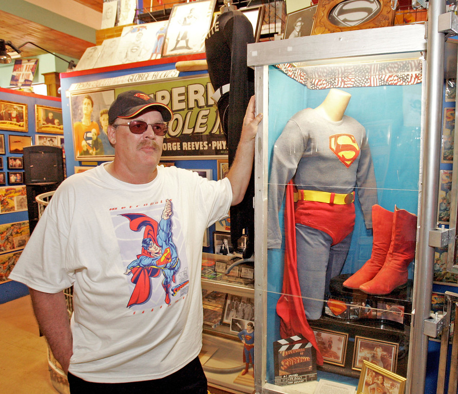 ". Jim Hambrick, the 51-year-old owner of a storefront shop and Superman Museum in Metropolis, Ill., stands in front a case containing one of the original Superman costumes, Saturday, June 9, 2005. Metropolis is the adopted home of Superman and is seeing an increase in tourists as a result of the upcoming movie ""Superman Returns,\"" which opens Wednesday, June 28, 2006, in U.S. theaters.  (AP Photo/James A. Finley)"