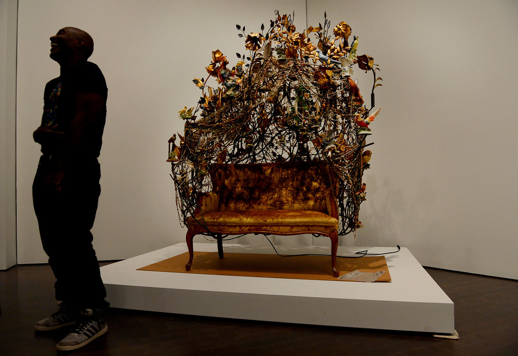 ". Artist Nick Cave stands infront of one of his sculptures while installing his exhibition ""Sojourn\"" at the Denver Art Museum in Denver, CO May 28, 2013. The exhibit includes a passageway constructed of thousands of buttons; large-scale, sculptural objects made out of found objects; more than 20 new Soundsuits; and a short film. (Photo By Craig F. Walker/The Denver Post)"