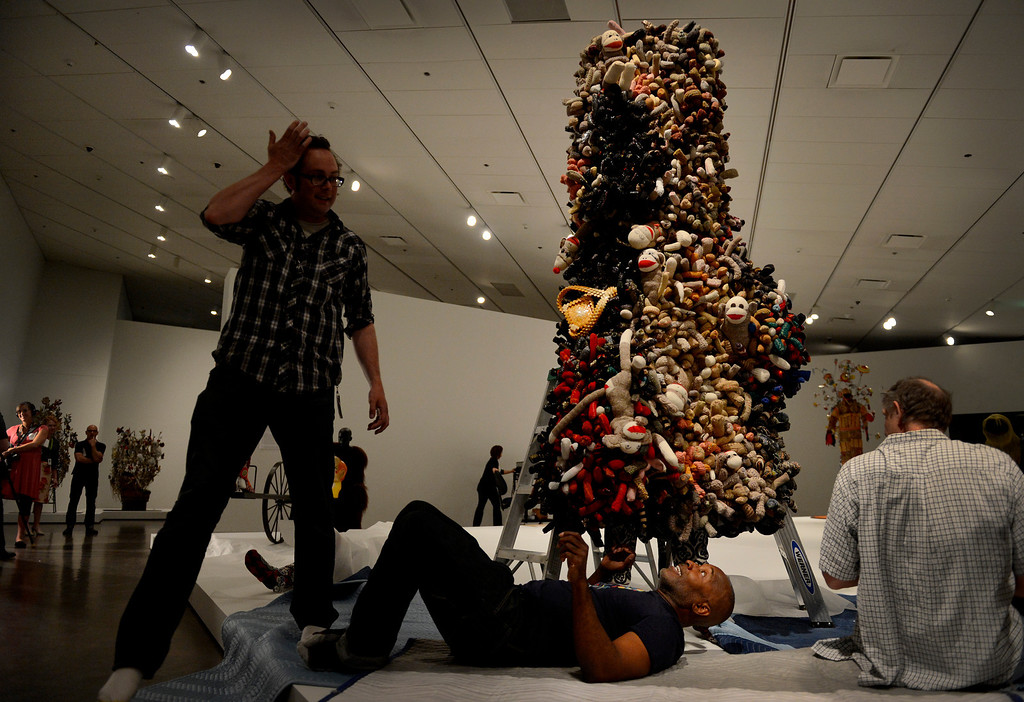 ". Artist Nick Cave, center, works on a Soundsuit while installing his exhibition ""Sojourn\"" at the Denver Art Museum in Denver, CO May 28, 2013. The exhibit includes a passageway constructed of thousands of buttons; large-scale, sculptural objects made out of found objects; more than 20 Soundsuits; and a short film. (Photo By Craig F. Walker/The Denver Post)"