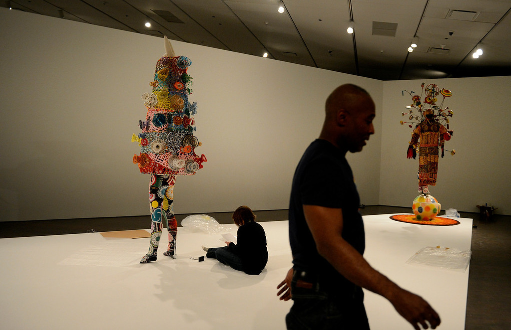 ". Artist Nick Cave works on Soundsuits while installing his exhibition ""Sojourn\"" at the Denver Art Museum in Denver, CO May 28, 2013. The exhibit includes a passageway constructed of thousands of buttons; large-scale, sculptural objects made out of found objects; more than 20 Soundsuits; and a short film. (Photo By Craig F. Walker/The Denver Post)"
