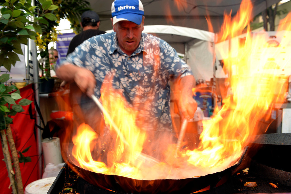 . Jason Barnett of Island Noodles gets the heat going on the wok as he stir fry\'s noodles and vegetables at the Cherry Creek Arts Festival June 7, 2013 in Cherry Creek North. The festival has been going on for three days during the July 4th holiday weekend since 1991, Colorado\'s signature cultural event. (Photo By John Leyba/The Denver Post)