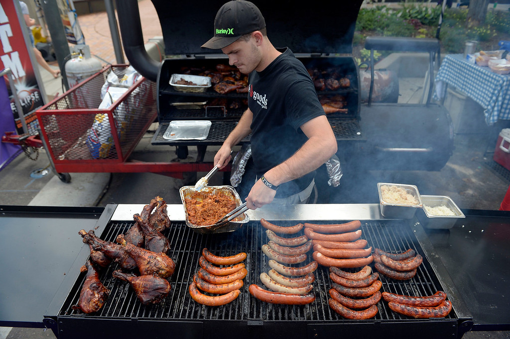. Cameron Russell of Teh goods Smoke & Grill heats up the brisket on the grill at the Cherry Creek Arts Festival June 7, 2013 in Cherry Creek North. The festival has been going on for three days during the July 4th holiday weekend since 1991, Colorado\'s signature cultural event. (Photo By John Leyba/The Denver Post)