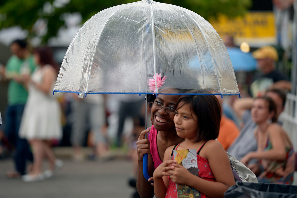 . Carol Reed 32, and Lizzy Montiel 10, take cover under an umbrella during a light drizzle at the Cherry Creek Arts Festival June 7, 2013 in Cherry Creek North. The festival has been going on for three days during the July 4th holiday weekend since 1991, Colorado\'s signature cultural event. (Photo By John Leyba/The Denver Post)