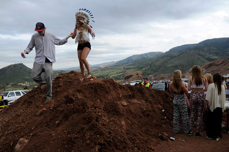 . Scottie Bolin, 19, of Charlottesville, Virginia, and Rachele Foos, 18, of Littleton, Colorado make their way off the top of a dirt as fans party in the lower south lot at Red Rocks Amphitheatre before the Global Dub Festival on May 16, 2014 in Morrison, Colorado. (Photo by Seth McConnell/The Denver Post)
