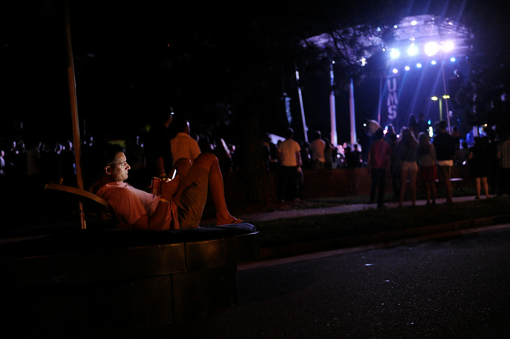 . Doug Varner relaxes on a bench as he listens to People Under the Stairs perform on the Main Stage during the Underground Music Showcase on July 25, 2014 in Denver, Colorado. (Photo by Seth McConnell/The Denver Post)