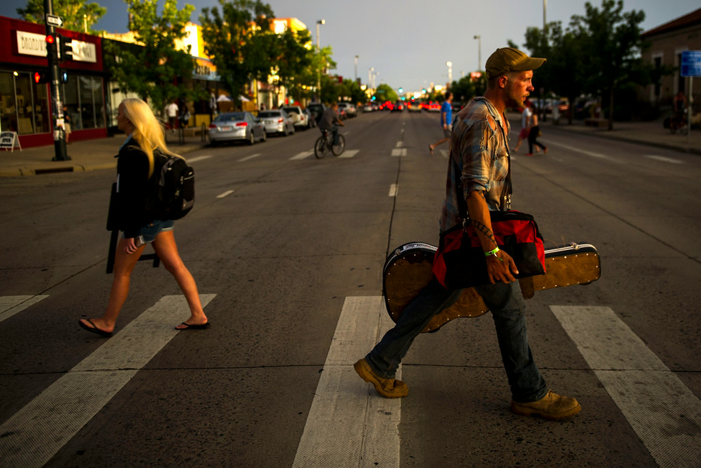 . Joe Cheves walks across the street after finishing a set at Gary Lee\'s Motor Blue and Grub along South Broadway during the Annual Underground Music Showcase on Friday, July 25, 2014 in Denver, Colorado.      (Photo by Kent Nishimura/The Denver Post)