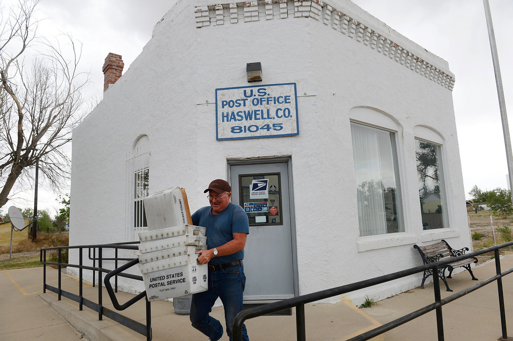 . HASWELL, CO - MAY 29:  Contract mail carrier, Mike Stiles, carries boxes of mail to his truck in front of the Haswell Colorado Post Office Wednesday May 29, 2013. (Photo By Andy Cross/The Denver Post)