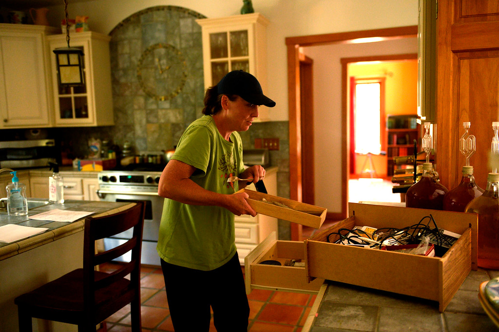 . COLORADO SPRINGS, CO. - June 14: Deanna Martin fills a drawer with the families account info and passwords and videos of her 2 children\'s childhood in the home she and her husband Troy built as some residents were allowed back into the Black Forest Fire area to quickly get medications and important items that were left behind in the rush to evacuate near Colorado Springs, Colorado. June 14, 2013 Denver, Colorado Springs. (Photo By Joe Amon/The Denver Post)