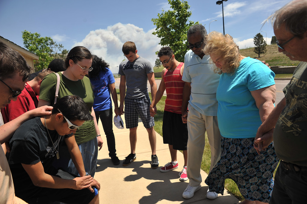 . COLORADO SPRINGS, CO. - June 12: From right, Black Forest Fire evacuees Larry and Deborah Bowin, Rev. Jimmy Lilley, volunteers from the church and 8 foster children are praying at the parking of Walmart in Colorado Springs. Colorado. June 12, 2013. The couple and 8 foster children spend over night at the parking. (Photo By Hyoung Chang/The Denver Post)