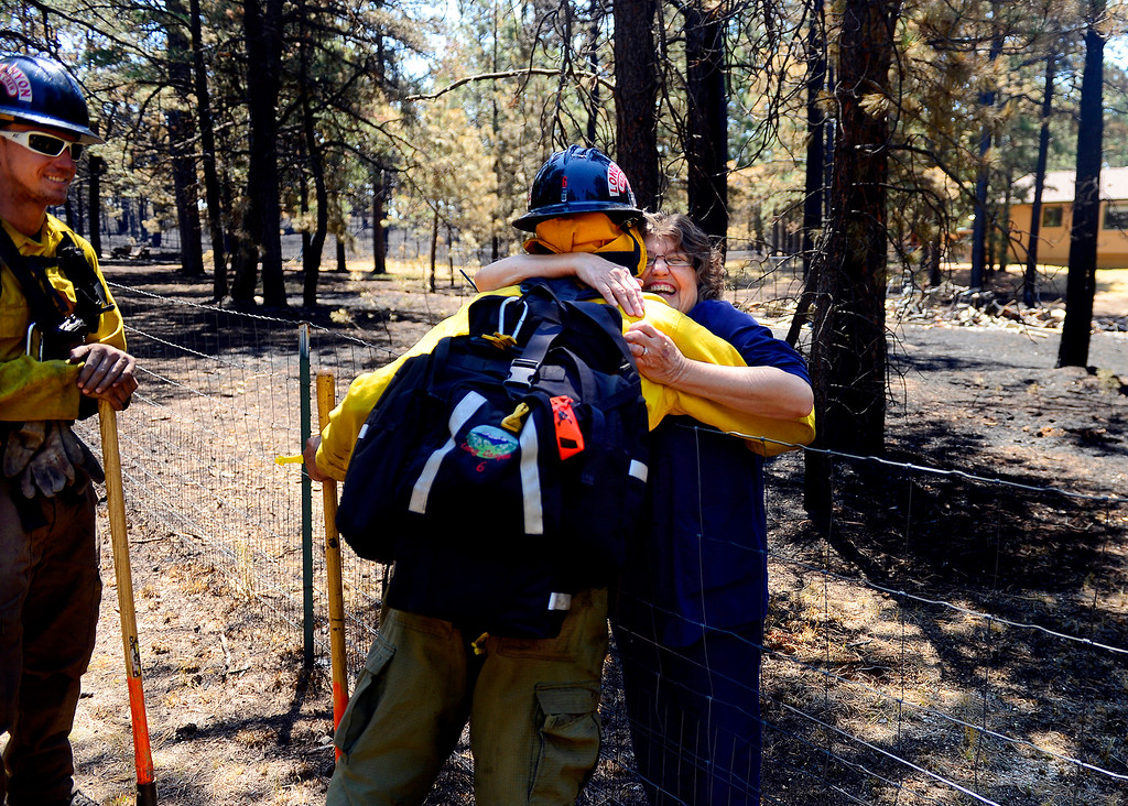 . Long Canyon Wildland firefighter Lynn Reynolds is hugged by homeowner Jody Wallace as he and his crew look for hot spots at a burned property on Pine Glen Drive. Only one home on the loop of Pine Glen Drive burned in the fire, and Wallace wanted to personally thank the firefighters for saving her adjacent home.