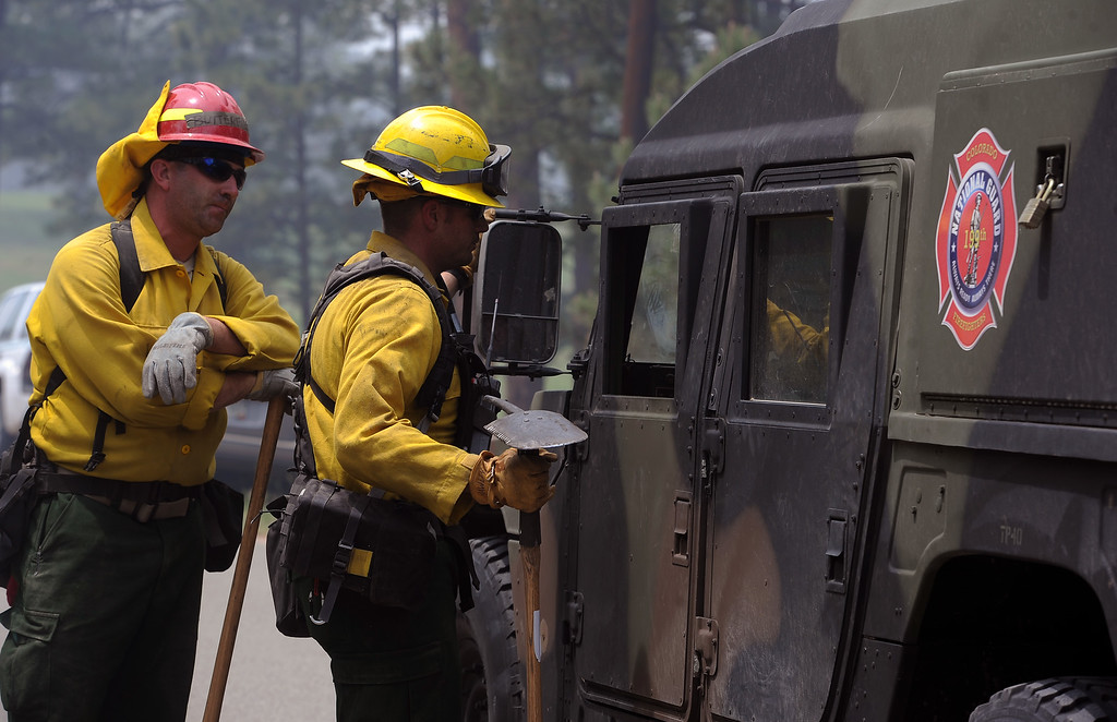 . Sgt. Ryan Hawley, right and Specialist Chris Butterfield, left, talk with crew members to decide their next move near Winchester Road north of Hodgen Road in the midst of the Black Forest Fire on June 13, 2013.  They are with the National Guard out of Fort Carson.  Photo by Helen H. Richardson/The Denver Post)