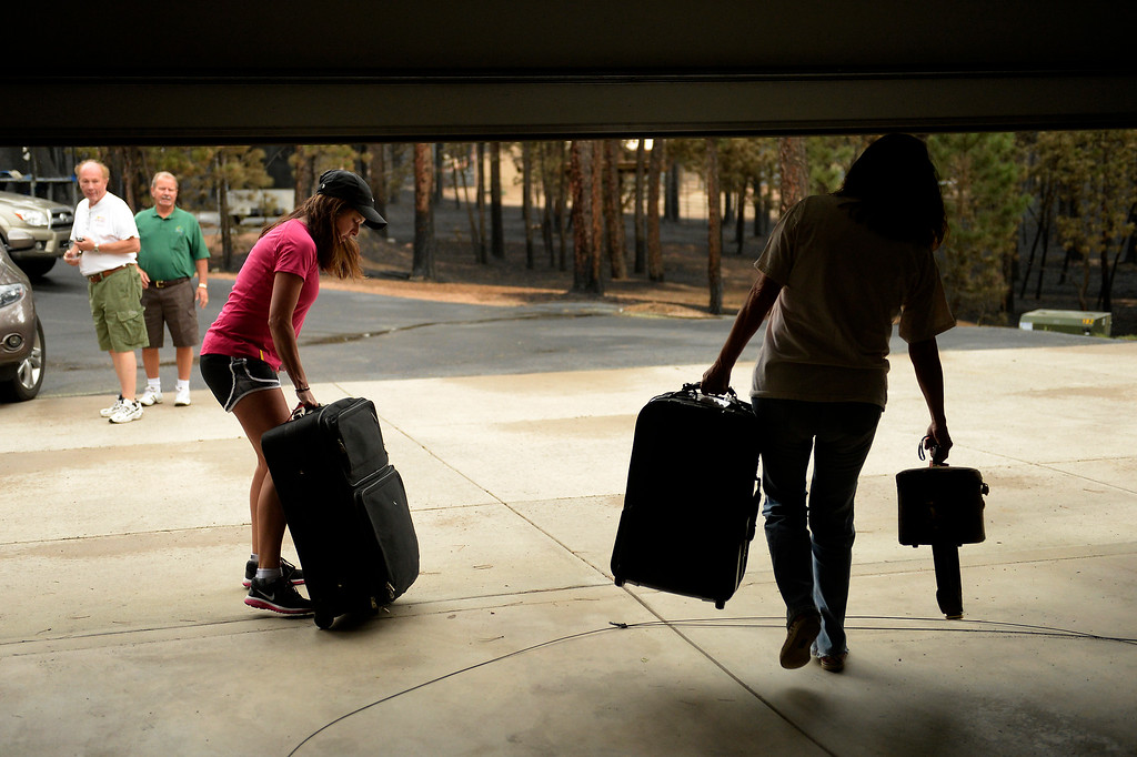 . COLORADO SPRINGS, CO. - June 14: Alicia Taylor and her mother Lana Forey hurry from their house with their bags as some residents were allowed back into the Black Forest Fire area to quickly get medications and important items that were left behind in the rush to evacuate near Colorado Springs, Colorado. June 14, 2013 Denver, Colorado Springs. (Photo By Joe Amon/The Denver Post)