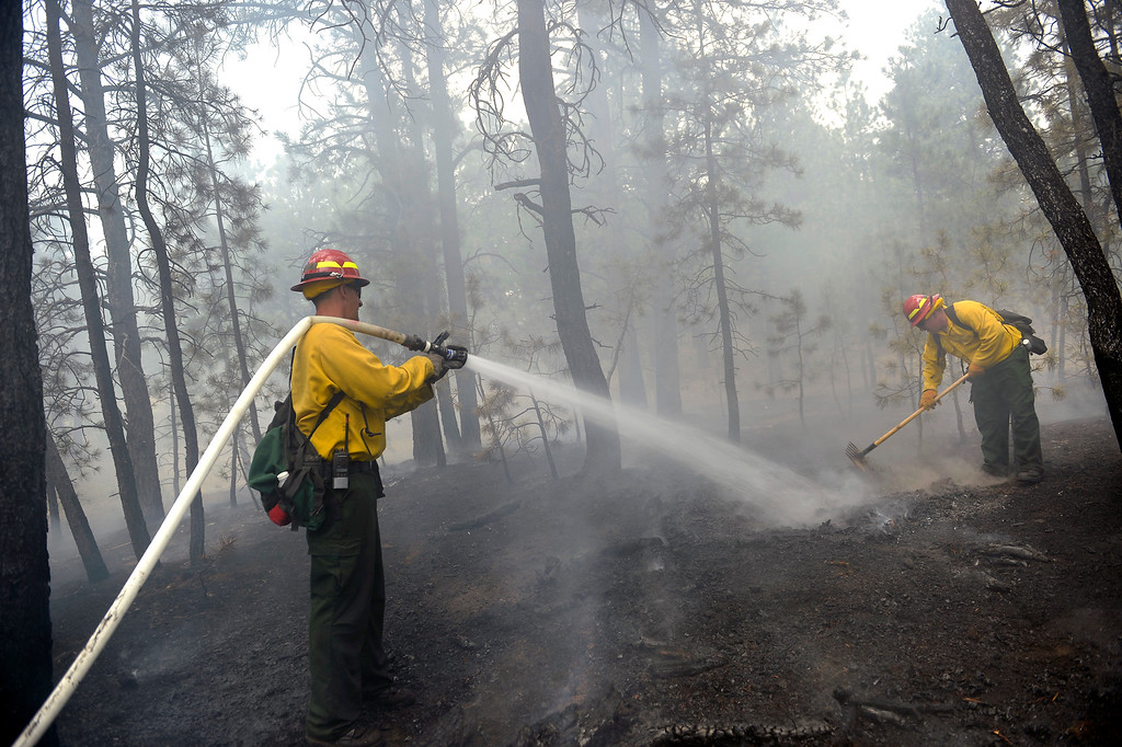 . st Sgt John Screiber, left, helps puts water on hotspots while Sgt David Meggison, left uses his tool to do the same thing puts   on property along Winchester Road north of Hodgen Road in the midst of the Black Forest Fire on June 13, 2013. Photo by Helen H. Richardson/The Denver Post)