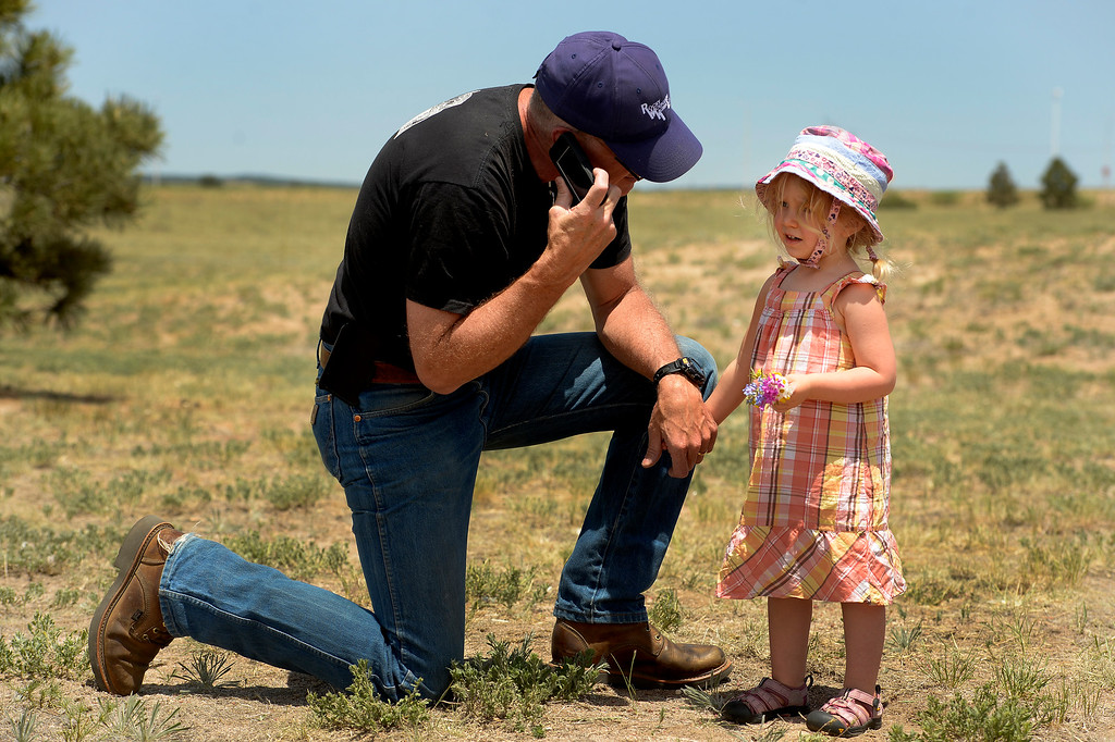 . Kerry Abernathy holds the hand of granddaughter Saylor Brown, 2, as he listens to the press briefing on his phone.  He and other Black Forest evacuees came to hear officials talk to members of the the media on the status of the Black Forest Fire  at Pikes Peak Community College Rampart Range Campus near Monument, CO  on June 15, 2013.  Abernathy did not lose his house but many of his neighbors did.  He is a builder and pledged to help as many people as he could to rebuild their homes and lives.  Photo by Helen H. Richardson/The Denver Post)
