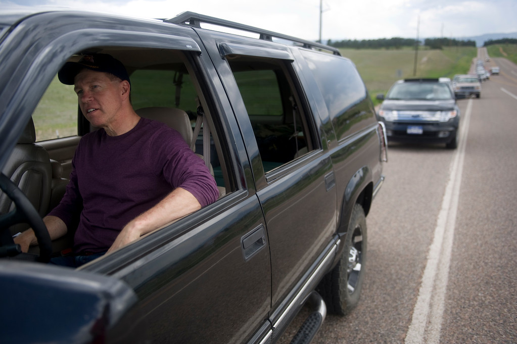 . Dan Bartlett waits in line at Highway 83 and Hodgen Road to be escorted to his home in Black Forest by police on Saturday, June 15, 2013. Police were only letting residents in with proof of residence for pets or medications. Cars in the front of the line had been waiting for upwards of three hours for their escort.(Photo By Grant Hindsley / The Denver Post)