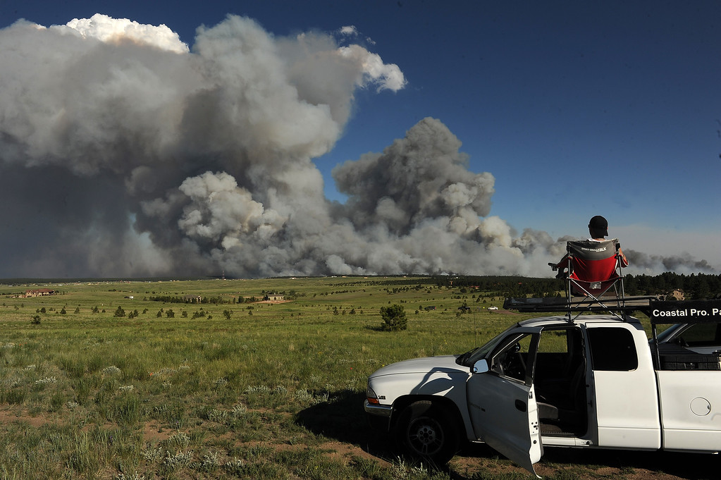 . COLORADO SPRINGS, CO - JUNE 11: Shaun Buhrman, of Aurora, watches the fire from a high meadow north of the fire. A wild land fire started around 2:00 in the Black Forest northeast of Colorado Springs, CO on June 11, 2013.  Homes have already burned and the wind is expected to continue through the afternoon.  Photo by Helen H. Richardson/The Denver Post)