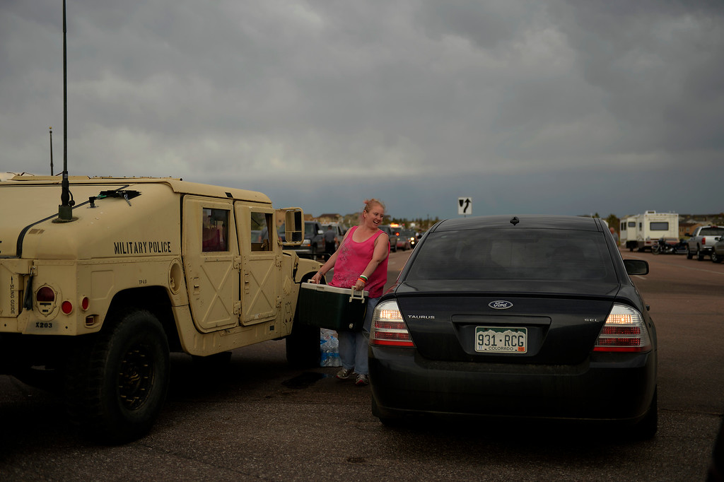""". COLORADO SPRINGS, CO. - June 14: Nicolette Dimaggo grabs her cooler after her escort into the Black Forest Fire area to quickly get medications and important items that were left behind in the rush to evacuate near Colorado Springs, Colorado. Nicolette drove for over four hours delivering drinks and snacks to all of the National Guardsmen, firefighters and police she could find, They saved my home,\"""" she said.  June 14, 2013 Denver, Colorado Springs. (Photo By Joe Amon/The Denver Post)"""
